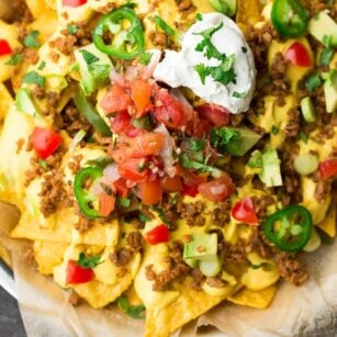 square image of vegan nachos on a plate with parchment paper