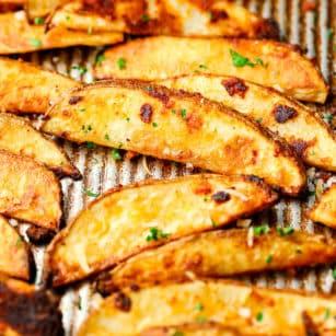 square photo of many potato fries on a pan