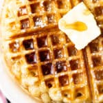close up square image of a waffle with butter