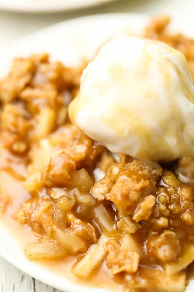 very close up of apple crisp on a plate with ice cream