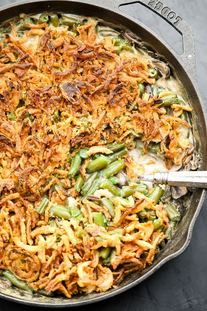 looking down on a cast iron pan filled with green beans in sauce and fried onions