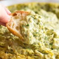 vegan spinach artichoke dip with a piece of bread dipped into it