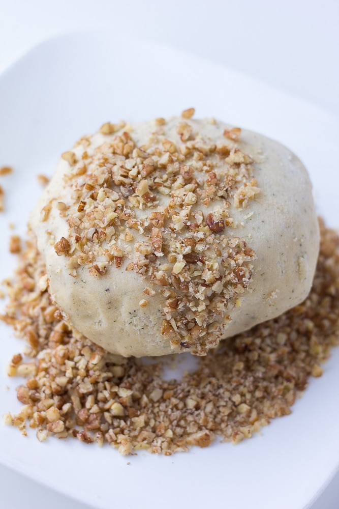 vegan cheese ball being rolled in nuts