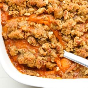 square image of casserole dish with sweet potatoes and pecan topping