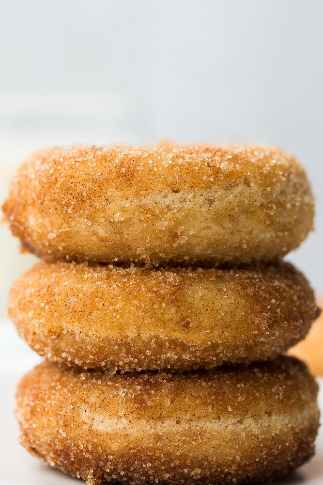 close up of 3 donuts stacked, grey background
