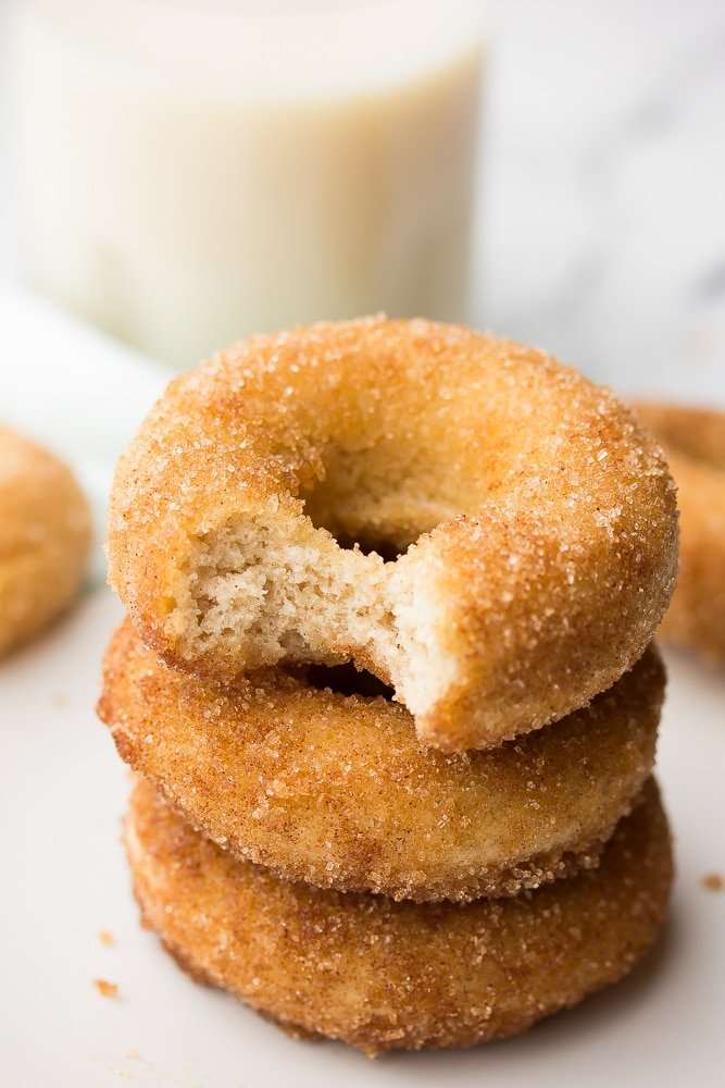 stack of donuts with a bite taken out of the top of one