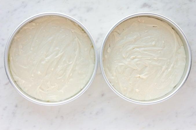 2 pans with uncooked vegan vanilla cake