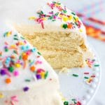 vegan vanilla cake with sprinkles on a cake plate