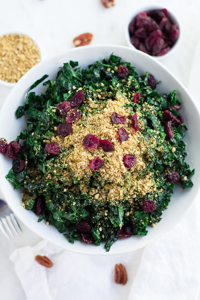 looking down on festive kale salad in white bowl