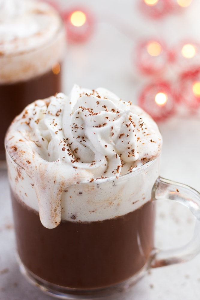 vegan hot chocolate with coconut whip cream, dripping down the cup