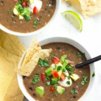 2 bowls of black bean soup with avocado, chips, tomatoes and cilantro