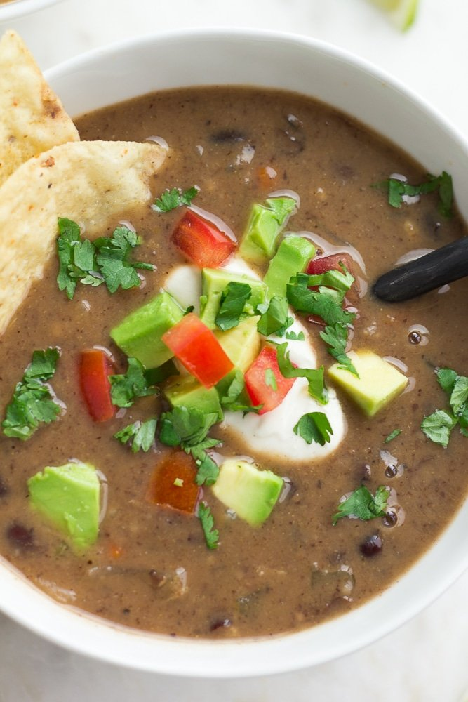 close up of bowl of black bean soup with sour cream, cilantro, chips and tomatoes