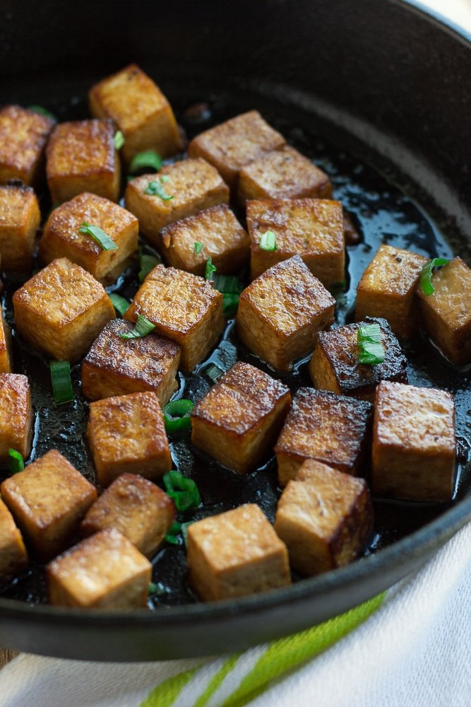 marinated tofu being fried in a cast iron pan