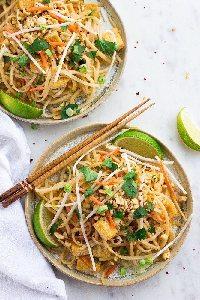 two plates with vegan pad thai from top with chopsticks