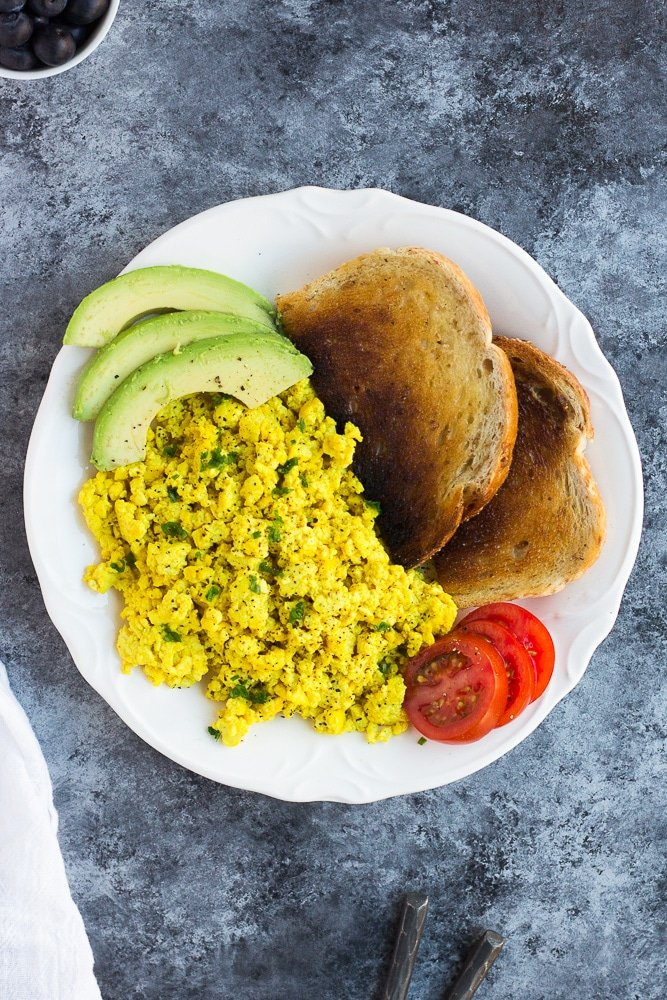 tofu scramble on a plate with avocado, tomato and toast