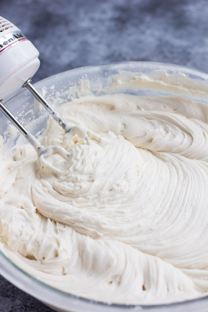 vegan cream cheese frosting in a bowl with a mixer, thick.