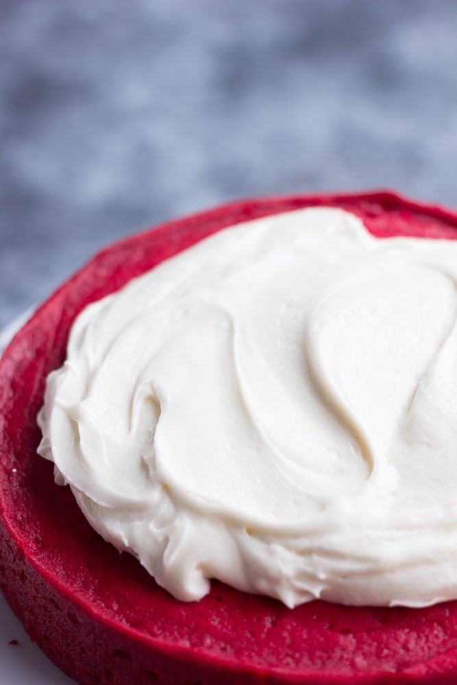 vegan cream cheese frosting being spread on a red cake.
