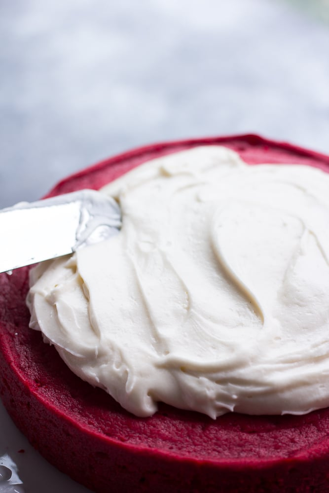 vegan cream cheese frosting being spread of vegan red velvet cake