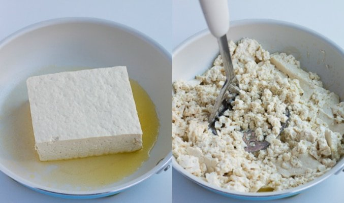 block of tofu in pan, then being pressed to crumble it for tofu scramble