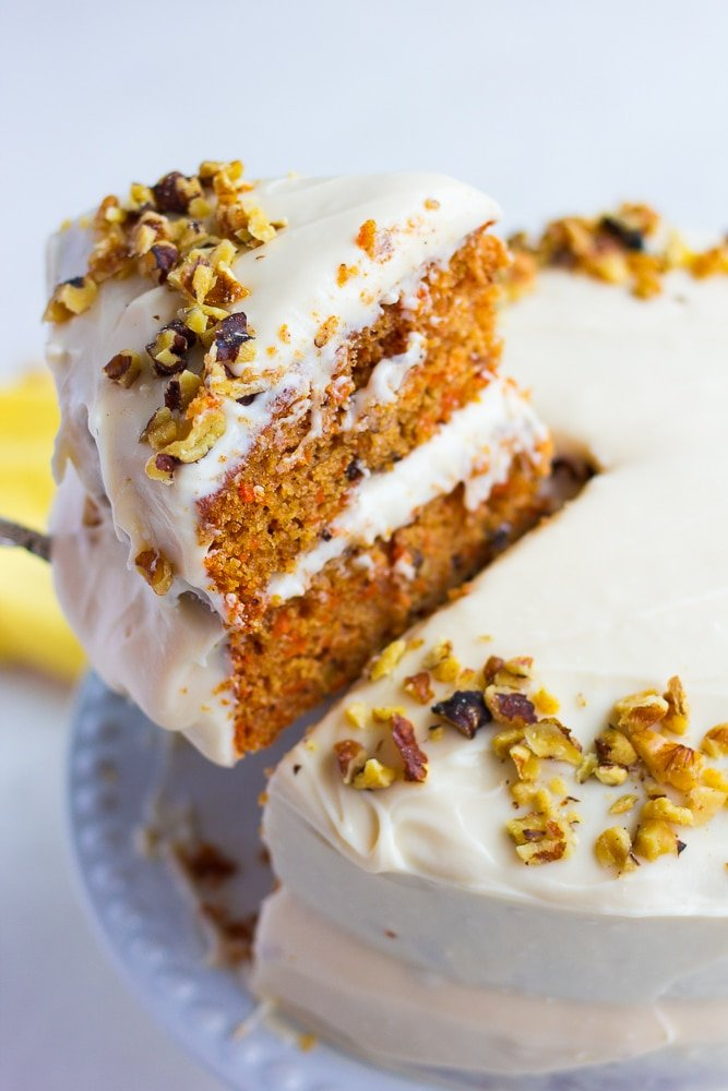 piece of vegan carrot cake being lifted out of whole cake