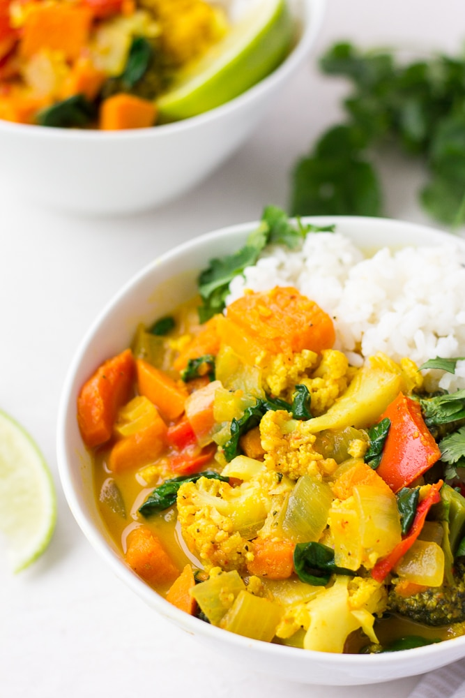 vegan curry in 2 bowls with white rice and cilantro