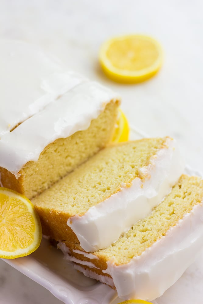 sliced lemon loaf with glaze and lemons in background