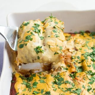 vegan enchiladas being lifted out of casserole dish