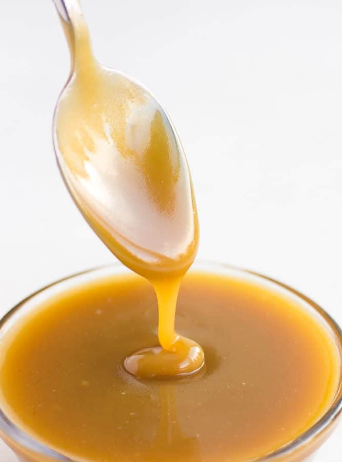 vegan caramel being drizzled with a spoon into a bowl of caramel.