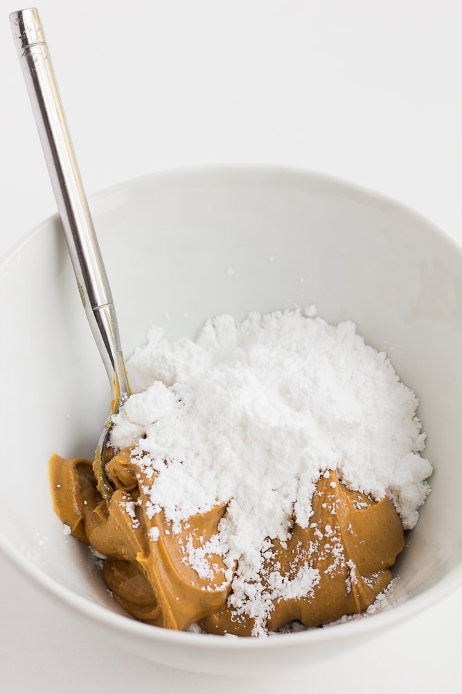 mixing peanut butter and powdered sugar in a bowl.
