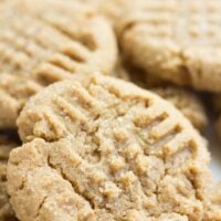 close up of vegan peanut butter cookie, with others behind it.