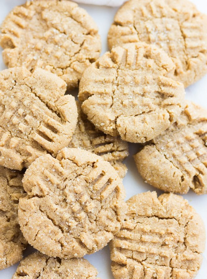 lots of vegan peanut butter cookies, on top of each other, white background.