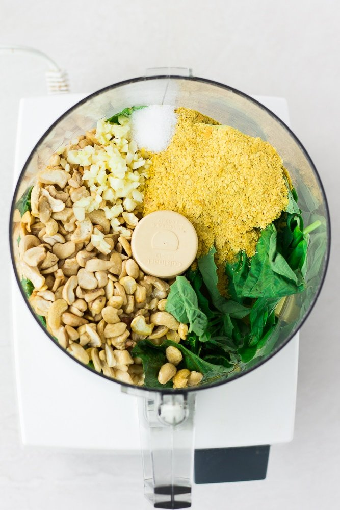 ingredients for vegan pesto in food processor before being blended.