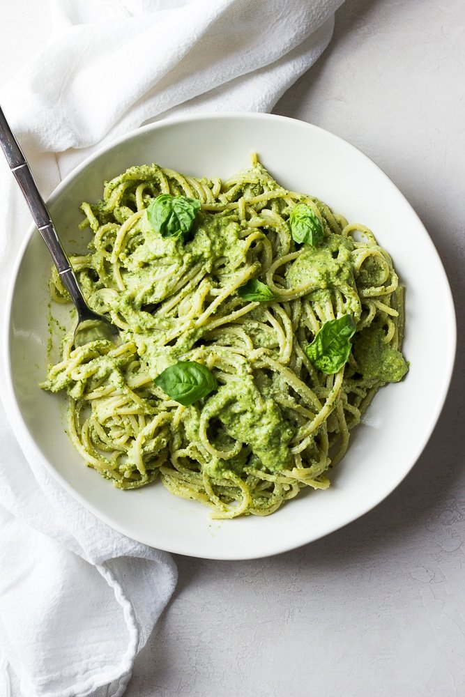 bowl of pasta drenched in pesto sauce, white bowl and background.