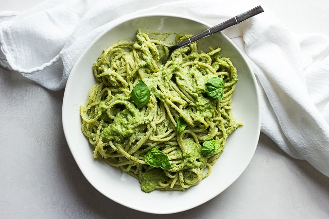 bowl of pasta drenched in vegan pesto, white bowl and background.