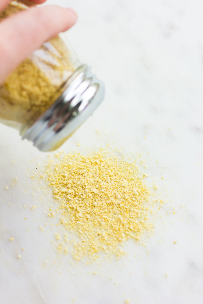 vegan parmesan being sprinkled out of container onto marble background.