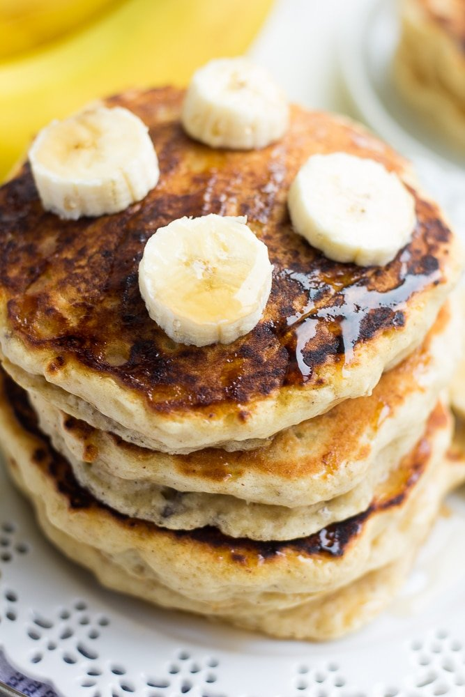 looking down on stack of banana pancakes with banana slices on top and syrup.