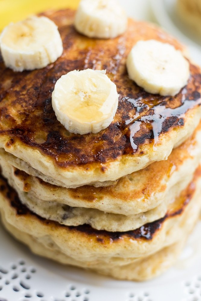 close up stack of vegan banana pancakes with banana slices on top.