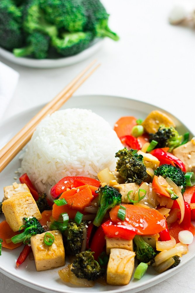 plate with scoop of white rice, tofu, vegetables and chopsticks.