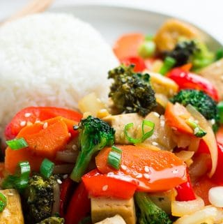 close up photo of tofu stir fry on a plate with rice and chopsticks.