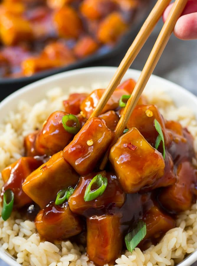 sriracha tofu being picked up with chopsticks from a bowl