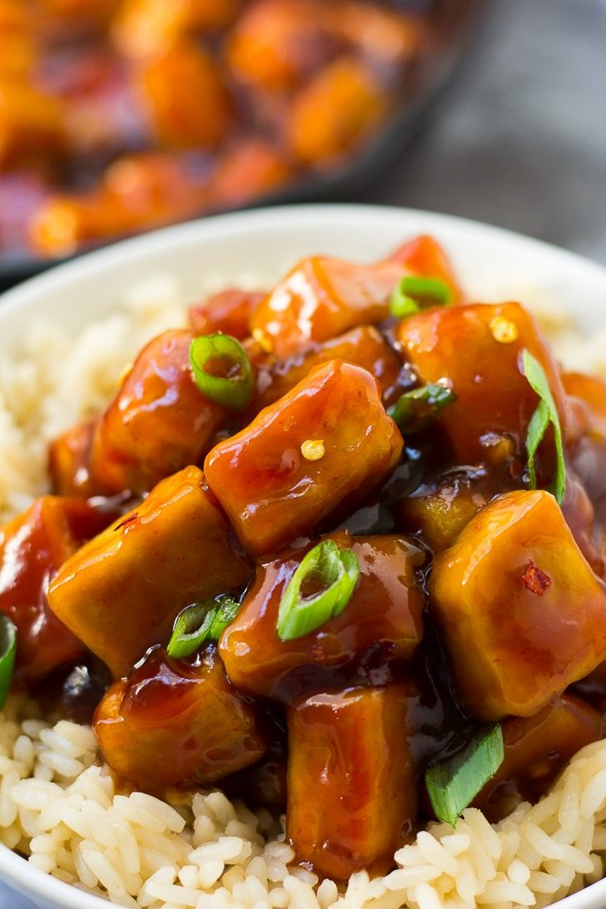 very close up photo of sriracha tofu in bowl with green onions