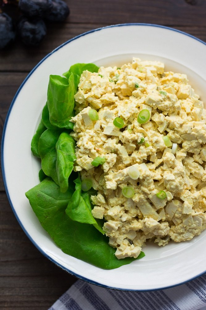 bowl of vegan egg salad with butter lettuce and wooden background