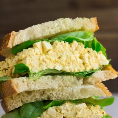 close up of vegan egg salad in a sandwich with lettuce.