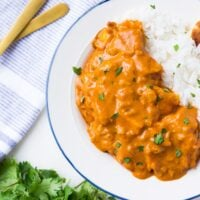 looking down on vegan butter chicken with rice, cilantro in background.