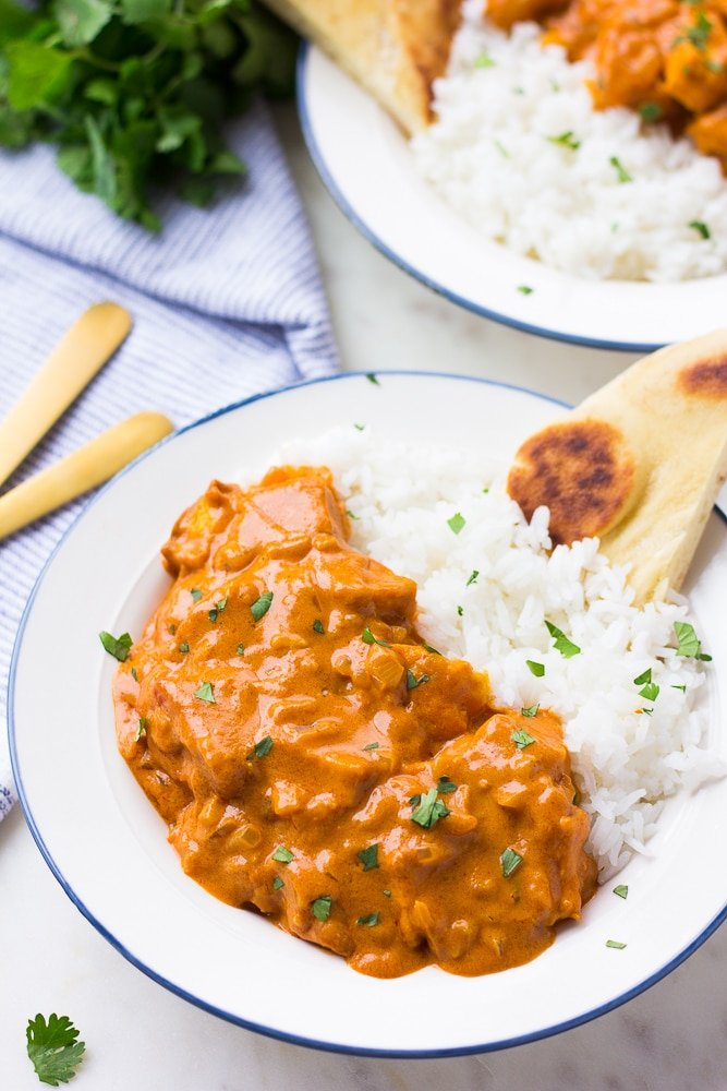 vegan butter chicken in a bowl with rice and naan