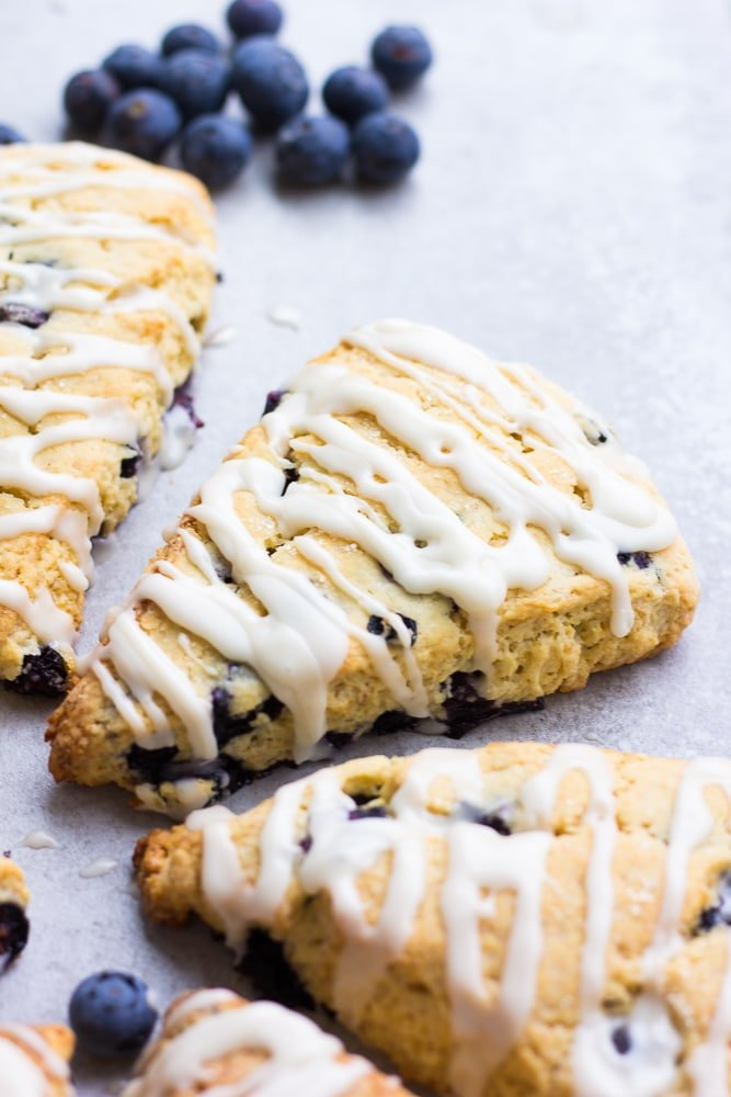 a couple of blueberry scones with glaze, grey background