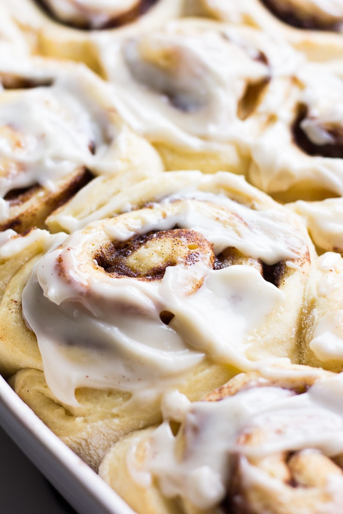 close up of vegan cinnamon roll with icing in a pan