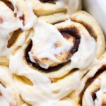 close up photo of vegan cinnamon roll with icing