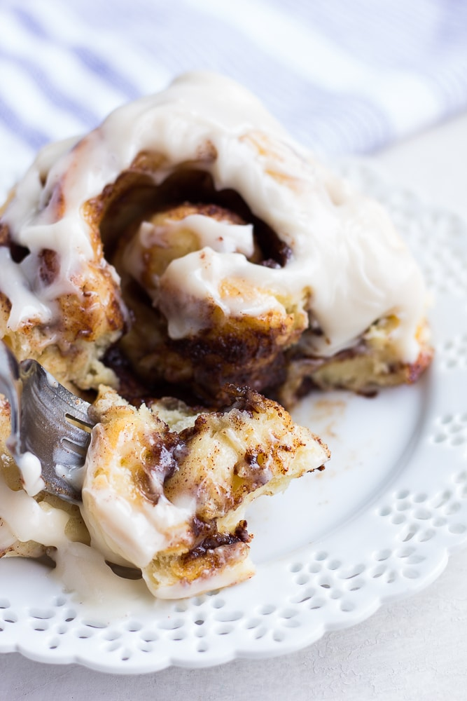 taking a bite of vegan cinnamon roll with a fork, insides exposed.
