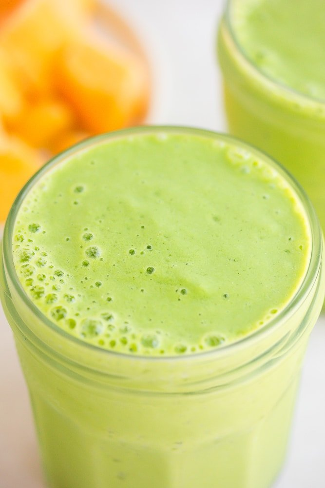 close up of vegan green smoothie with mango in background.